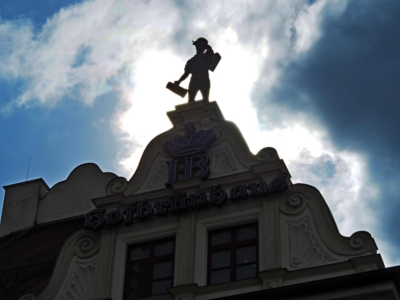 Ein Mensch aus Eisen mit Bier in der Hand: das muss ein Ironblogger sein.: gesehen auf dem Hofbräuhaus in München, vor weiß-blauem Himmel.