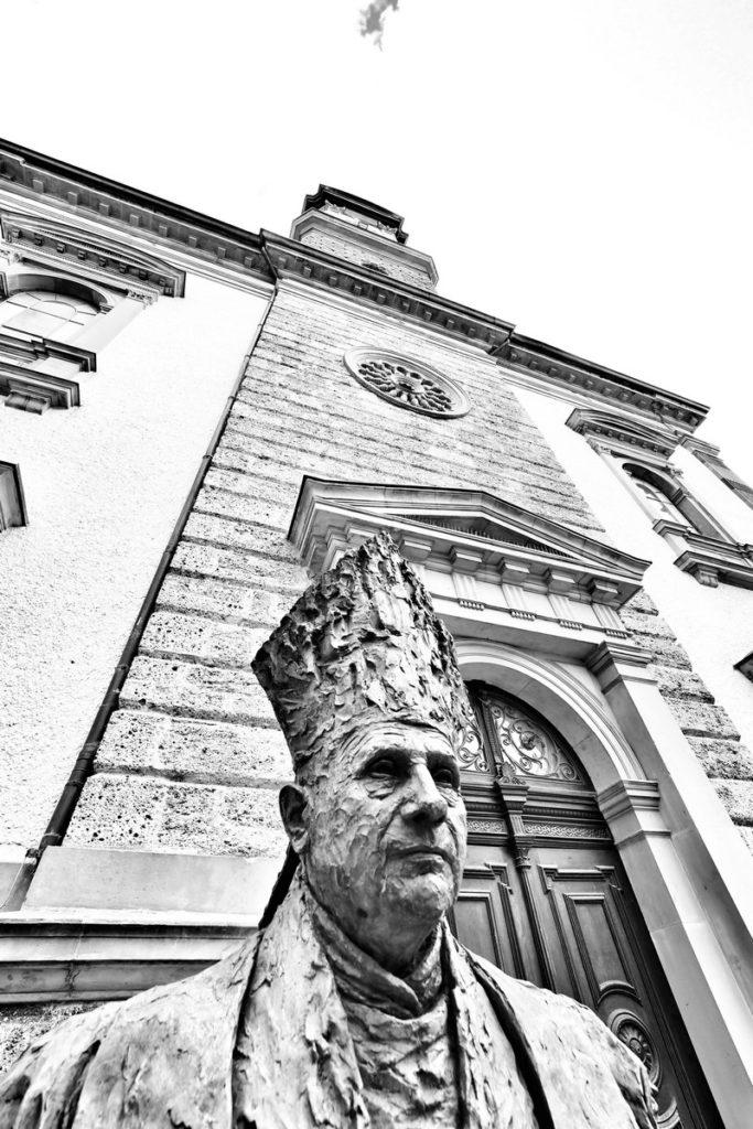 Papstbüste in der Vaterstadt Georg Ratzingers mit Pfarrkirche St. Oswald. Aufgenommen mit dem Olympus Pro 7-14mm/2,8